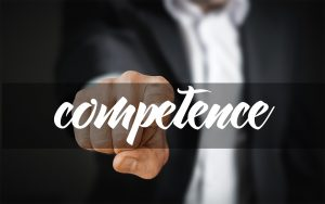 Person in a suit pointing to the word 'competence'