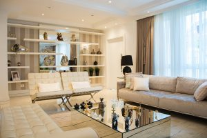 Beautiful white sitting area with mirror shelves and decorations on one wall.