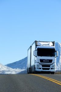 White truck on the road with snowy mountains in the background.