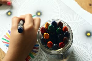 A close of a child coloring with crayons.
