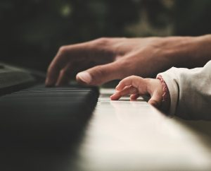 Baby and a father touching a piano.