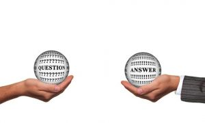 "Two hands holding ""question"" and ""answers"" globes"