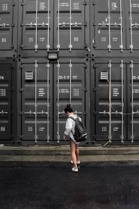 A girl in a gray top standing in front of a black storage unit
