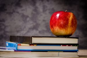 Books and apple on a school desk
