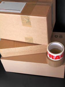 Cardboard boxes and tape. You'll definitely need these things to pack your belongings for storage in a day.