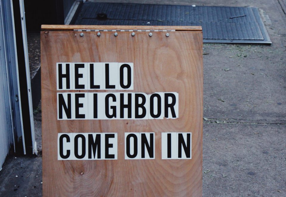 wooden board with hello neighbor come on in written on it