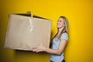 A woman holding a large cardboard box