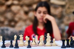 A girl thinking about her next chess move