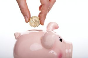 A person putting a coin into a piggy bank after implementing our decluttering tips